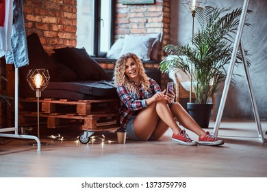 Pretty smiling woman is sitting next to the pallet sofa and holding her smartphone. She wear hotpants and checkered shirt. Modern loft with brick wall at background.