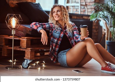 Pretty smiling woman is sitting next to the pallet sofa. She is holding cup of coffee. Woman wear hotpants and checkered shirt. Modern loft with brick wall at background.