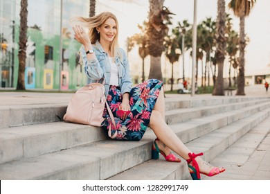 pretty smiling woman sitting on stairs in city street in stylish printed skirt and denim oversize jacket with leather backpack, summer style trend