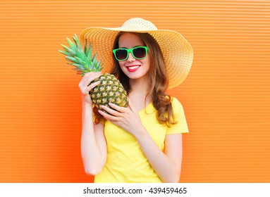 Pretty smiling woman in sunglasses and hat with pineapple over colorful orange background