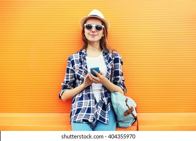 Pretty smiling woman using smartphone in city over orange background