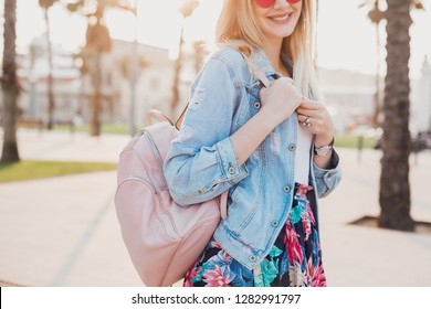 pretty smiling woman walking in city street in stylish denim oversize jacket, holding pink leather backpack, summer style trend