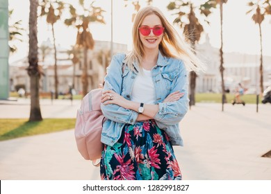 pretty smiling woman walking in city street in stylish printed skirt and denim oversize jacket wearing pink sunglasses, holding leather backpack, summer style trend