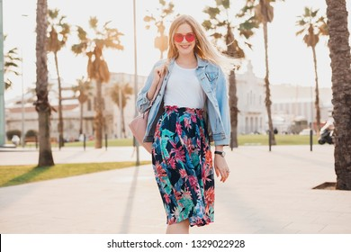 pretty smiling woman walking in city street in stylish printed skirt and denim oversize jacket wearing pink sunglasses, summer style trend