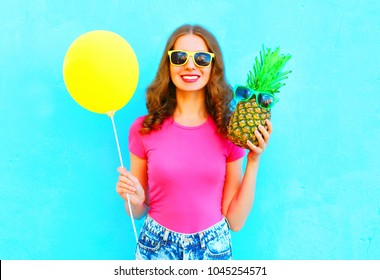 Pretty smiling woman with yellow air balloon and pineapple wearing a pink t-shirt over colorful blue background
