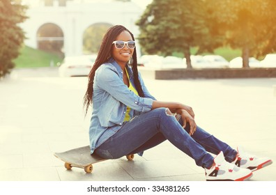 Pretty smiling young african woman with skateboard in city
