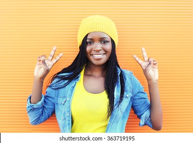 Pretty smiling young african woman having fun over orange background