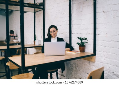 Pretty smiling young female sitting at wooden table in modern loft cafe browsing internet and watching funny video on laptop