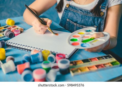 Pretty smiling young woman drawing a picture on white sheet
