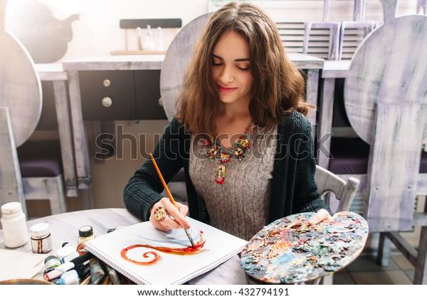 Ziemlich lächelnde junge Frau, die ein Bild mit Plakatfarbe zeichnet. Vordere Ansicht zum Zeichnen von Mädchen mit Palette in der Hand. Lächelnde junge Frau zeichnet ein Bild im Studio