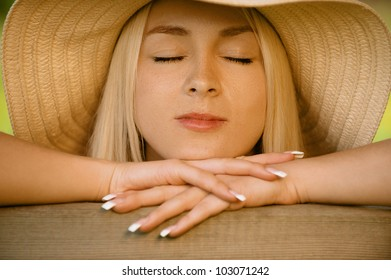 Pretty smiling young woman in hat sitting on wooden bench with closed eyes, against green of summer park.