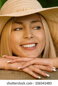 Pretty smiling young woman in hat sitting on wooden bench close up, against green of summer park.