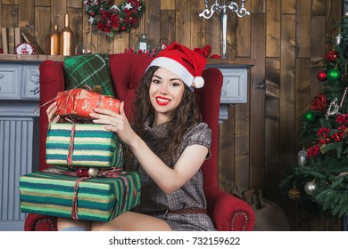 Pretty smiling young woman in red Santa's hat with long dark curly hair holds Christmas presents in boxes in hands near the Christmas pine tree. Tradition of giving presents