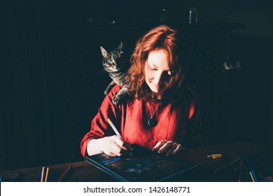 Pretty smiling young woman sketching at home. Front view on drawing girl with cat siting on a shoulder. Smiling young woman draw a picture at home.