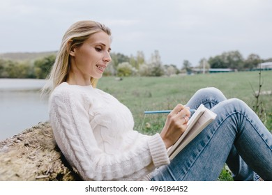Pretty smiling young woman in white sweater and blue jeans draws in a notebook with colored pencils sitting on the grass and leaned into the trunk of a dry tree on a background of lake