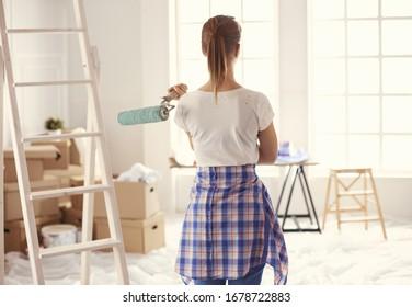 Una mujer muy tirita pintando la pared interior de la casa con rodillo de pintura