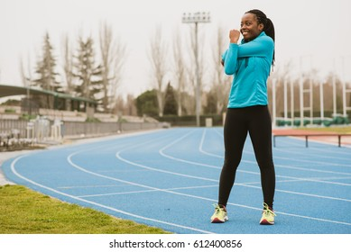 Pretty sporty African woman doing the fitness in the stadium. Horizontal outdoors shot.