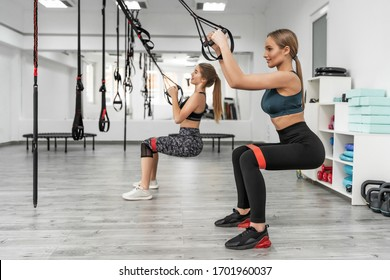 Pretty sporty girls training in fitness club with modern TRX equipment and performing squats with elastic band during effective full body workout.