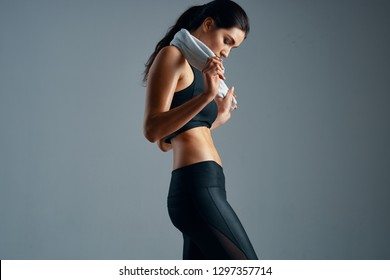 Pretty sporty woman in black leggings with a towel in her hands against a dark background