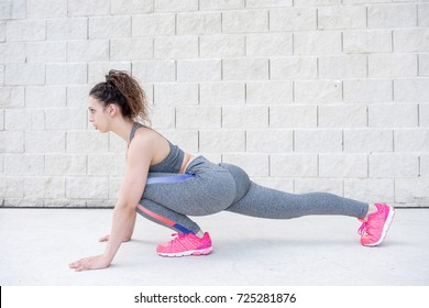 Pretty Sporty Woman Stretching Legs Near Brick Wall