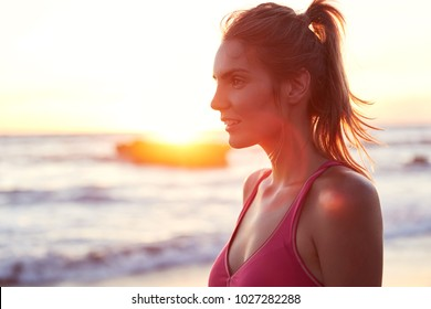 Pretty sporty woman in tracksuit stands sideways, enjoys beautiful sunrise on seashore, does sport exercises early in morning, spends vacations on tropical island. Fit female jogger outdoor.