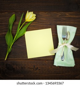 Pretty Spring Table Place Setting with Yellow Tulip, silverware, cloth napkin and a blank green menu card with room or space for copy, text or your words.