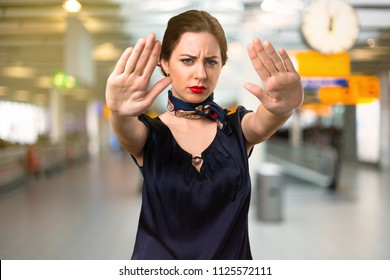 Pretty stewardess making stop sign inside the airport