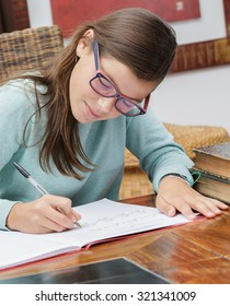 pretty student girl doing homework at home