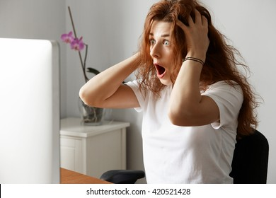 Pretty student girl having trouble with her laptop, looking in panic at the screen, holding her head. Frightened businesswoman with critical computer hanging problem. Negative human face expressions
