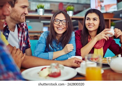 Pretty student having dinner and talking