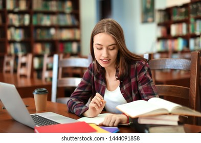 Pretty student with laptop studying in library