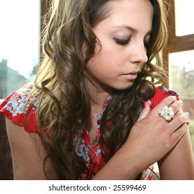 A pretty student looks at her pearl ring