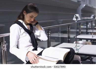 Pretty student sitting on desk in modern university library studying a book.