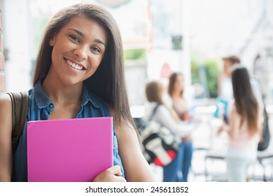 Pretty student smiling and holding notepads at the university