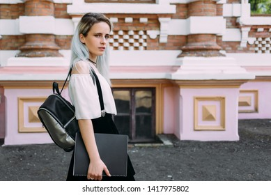 Pretty student stands with a black folder and a backpack against the background of the architektura. - Shutterstock ID 1417975802