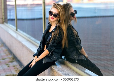 Pretty stylish blonde woman posing near mirrored city wall, urban city style, total black street style outfit, long hairs, fit sexy body, glamour vogue style.
