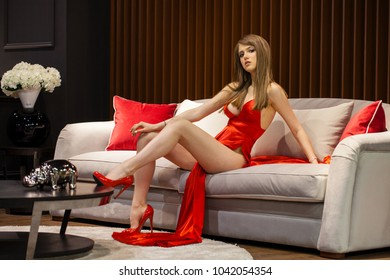 Pretty stylish blonde woman in red dress siiting in armchair on rich home interior background