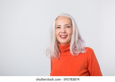 Pretty stylish grey haired woman in a red polo neck sweater standing with her hands to her throat smiling at the camera with a serene expression