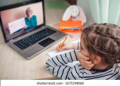 Pretty stylish schoolgirl studying homework math during her online lesson at home, social distance during quarantine, self-isolation, online education concept, home schooler