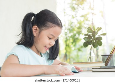 pretty stylish schoolgirl studying homework during online lesson at home, social distance during quarantine, self-isolation, online education concept, home school. girl does homework in her copybook