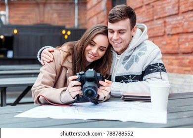 Pretty stylish sensual young couple in love are sitting at the table, drinking coffee and making pictures with dslr camera outdoor in cold winter weather