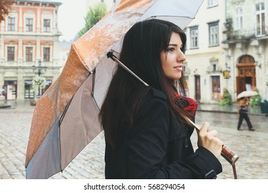 Pretty stylish woman in dark coat and red checkered scarf with umbrella. Romantic sad woman in the city.