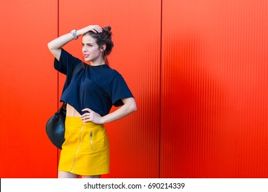 Pretty stylish woman standing against red wall