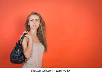 Pretty stylish young girl with a black bag on a red background with cooyspace