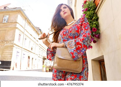 Pretty stylish young woman with beige leather handbag walking on the city streets. Plus size model in bright red dress. Casual street look.