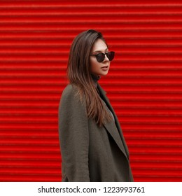 Pretty stylish young woman with sunglasses in fashion green coat on a red metal background