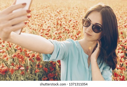 Pretty stylish young woman taking selfie with smartphone in poppies flowers meadow in spring outdoor.