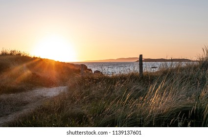 Pretty sunset and beach, taken from grassy sand dunes. Taken along the Wild Atlantic Way in County Galway, Ireland in summer.