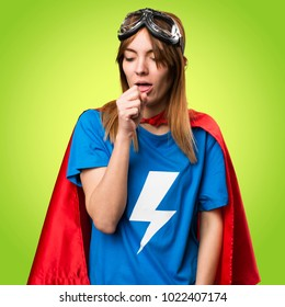 Pretty superhero girl coughing a lot on colorful background