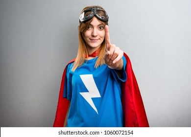 Pretty superhero girl counting one on a gray textured background